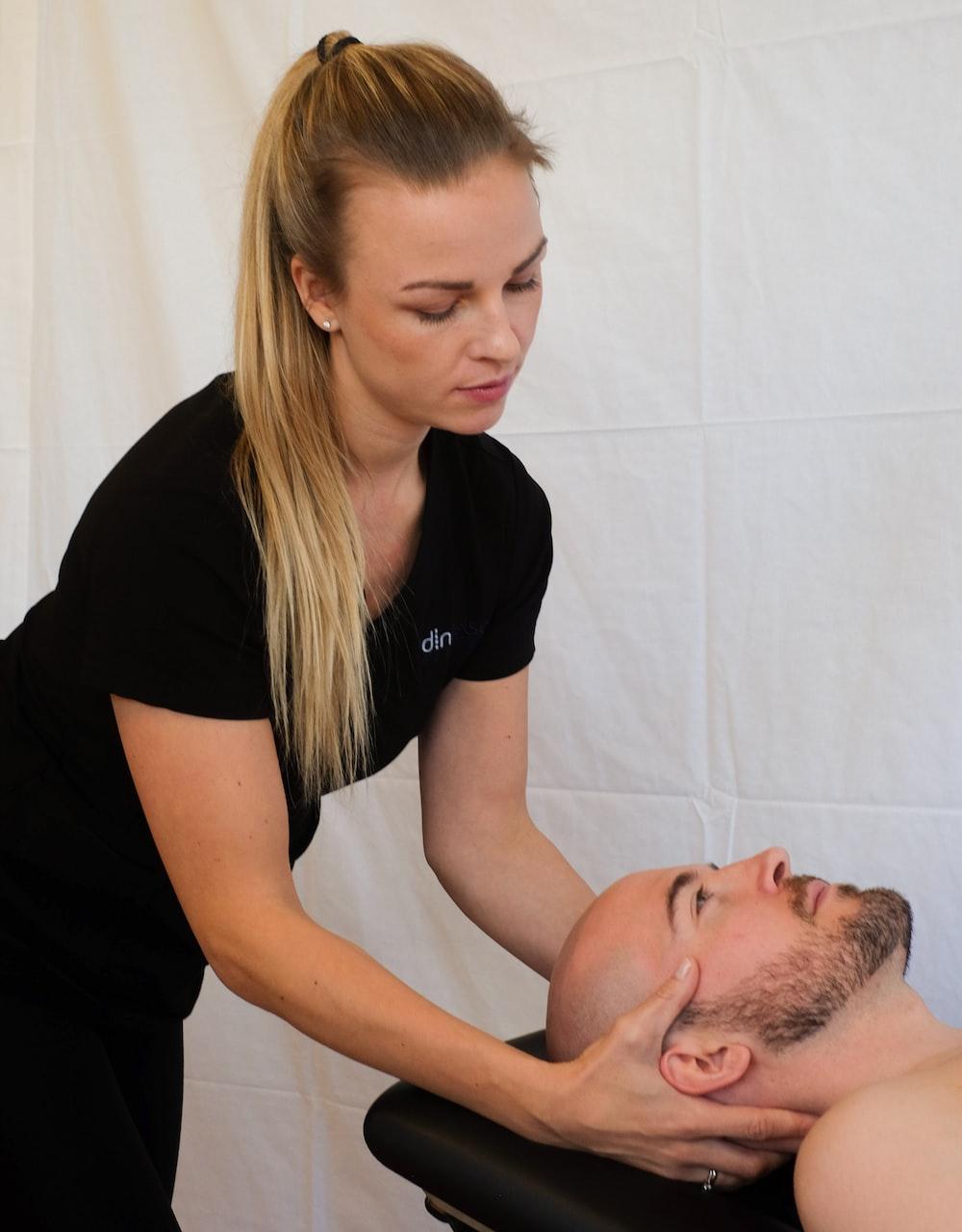 woman massaging man on head