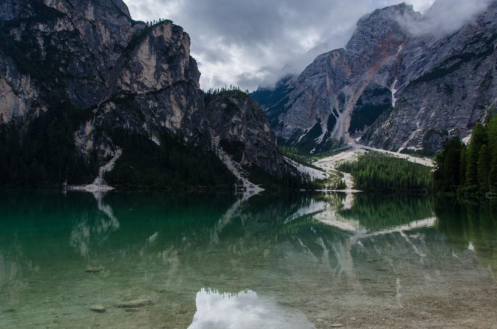 clear body of water beside mountain