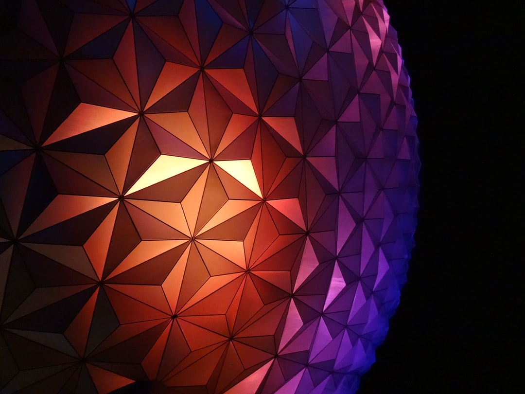 """The globe illuminates and pretty much transforms from this grey sphere into this """"tropical sunset"""" color gradient as the park gets ready to close its doors for the night."""