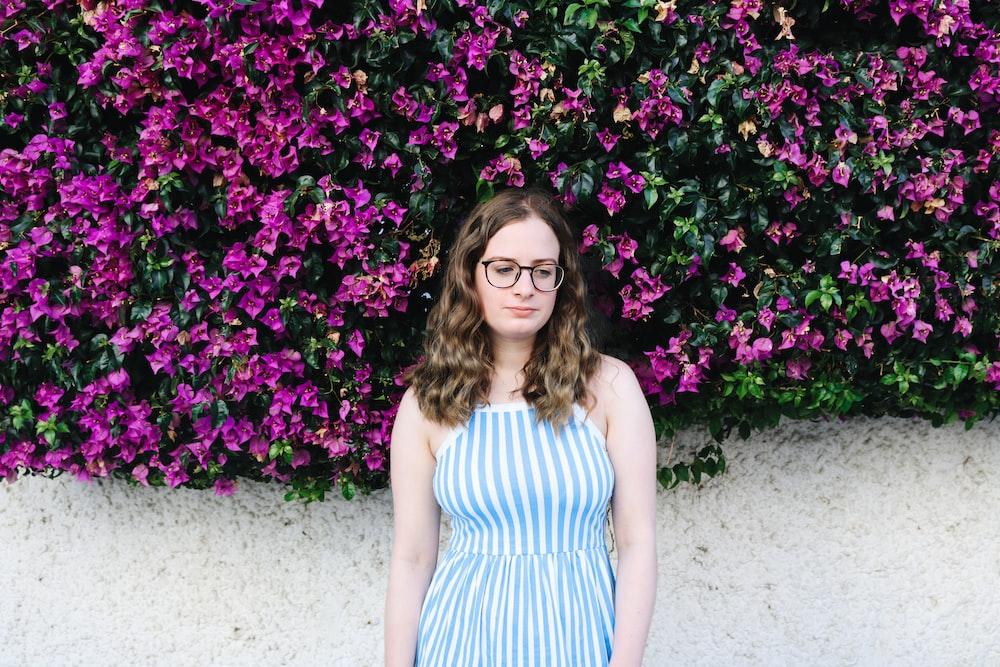 woman wearing blue dress standing in front of purple flowers