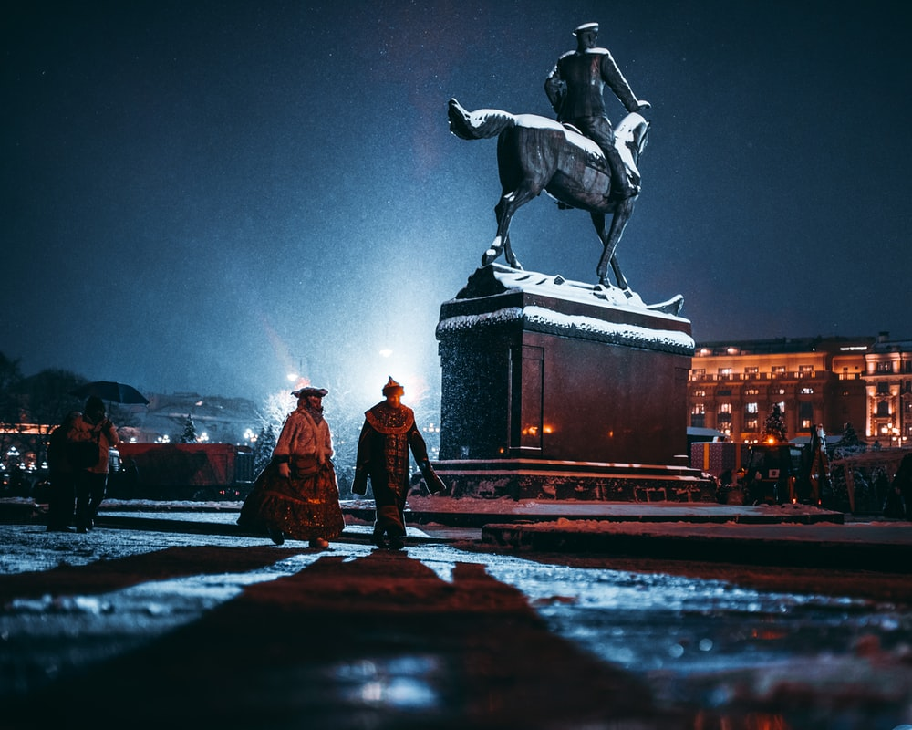 two person walking near person riding horse statue