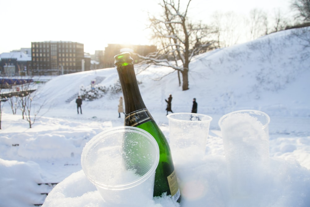 wine bottle beside disposable cups on snow