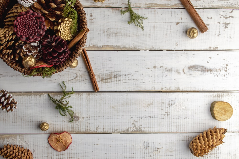assorted-color pine cones on white wooden surface