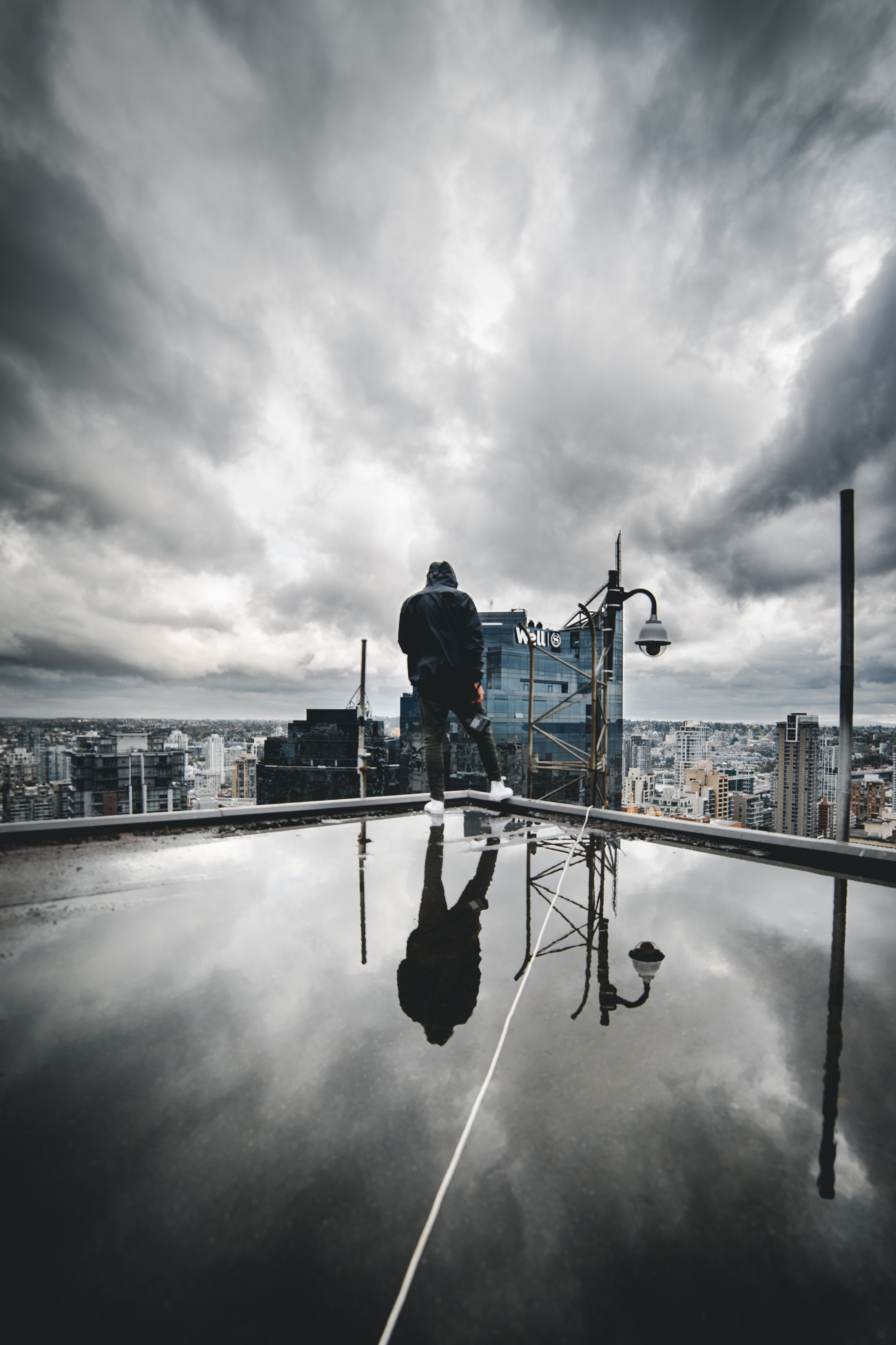 man standing on top of building under cloudy sky