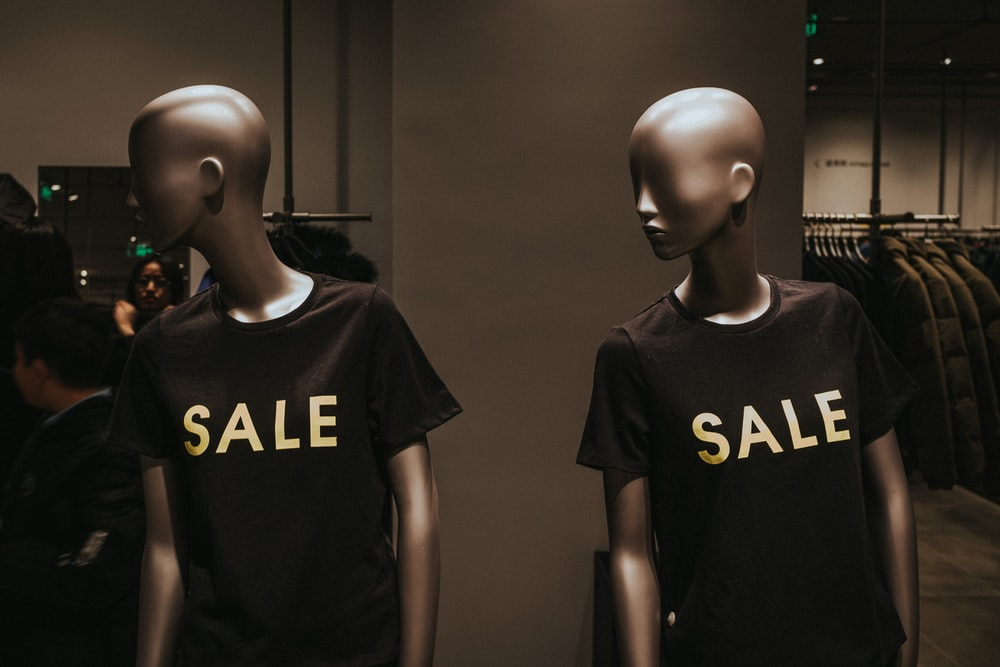 two mannequins with black Sale graphic crew-neck t-shirts