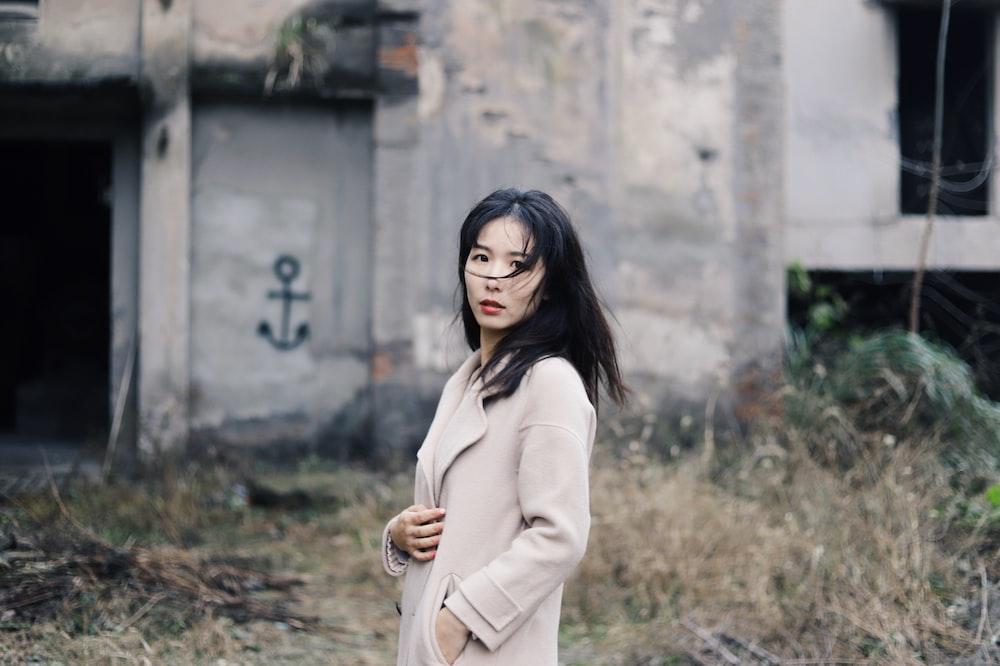 woman wearing beige coat standing near building ruins