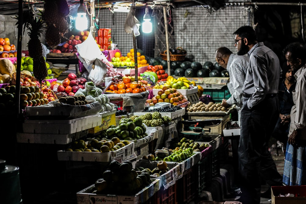 man standing in front of fruit stall