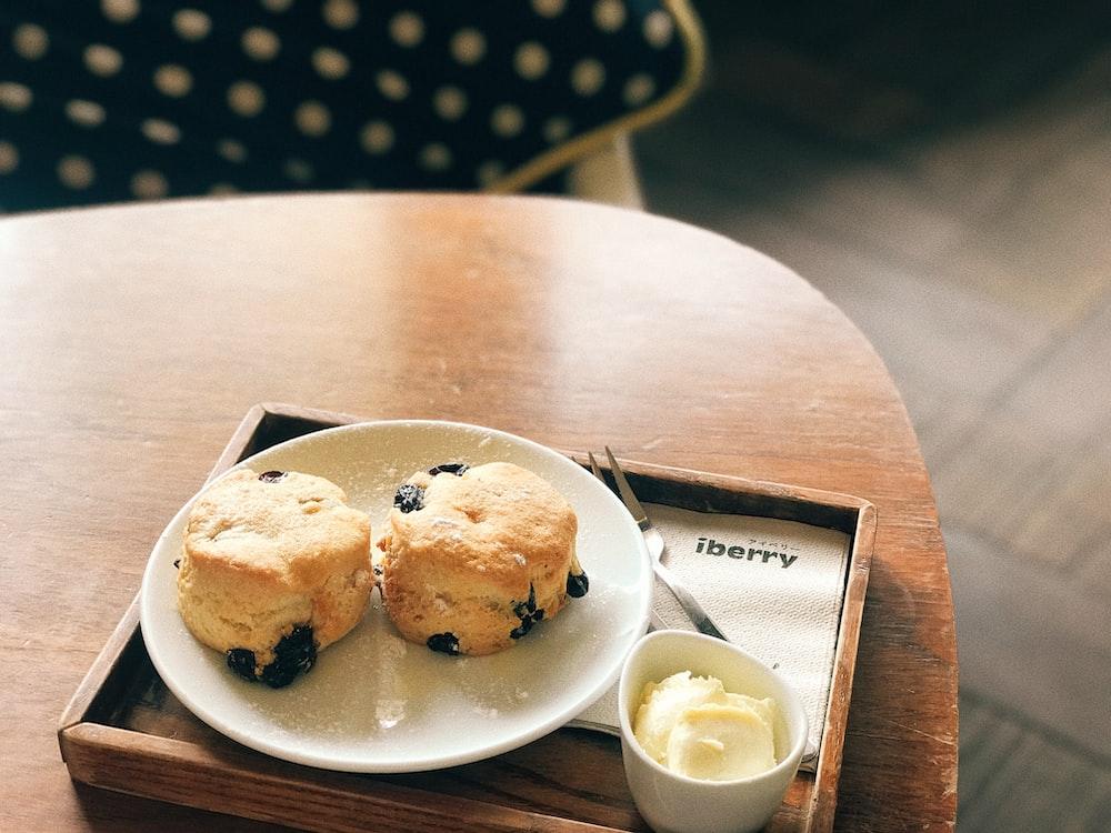 raisins bread on plate beside butter in bowl