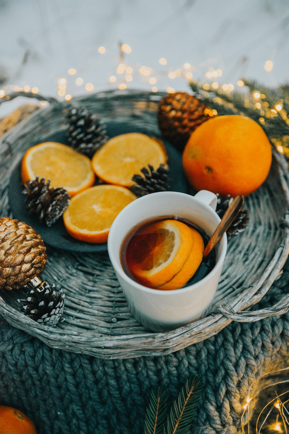 white ceramic mug filled with black liquid and sliced orange fruit on wicker food tray