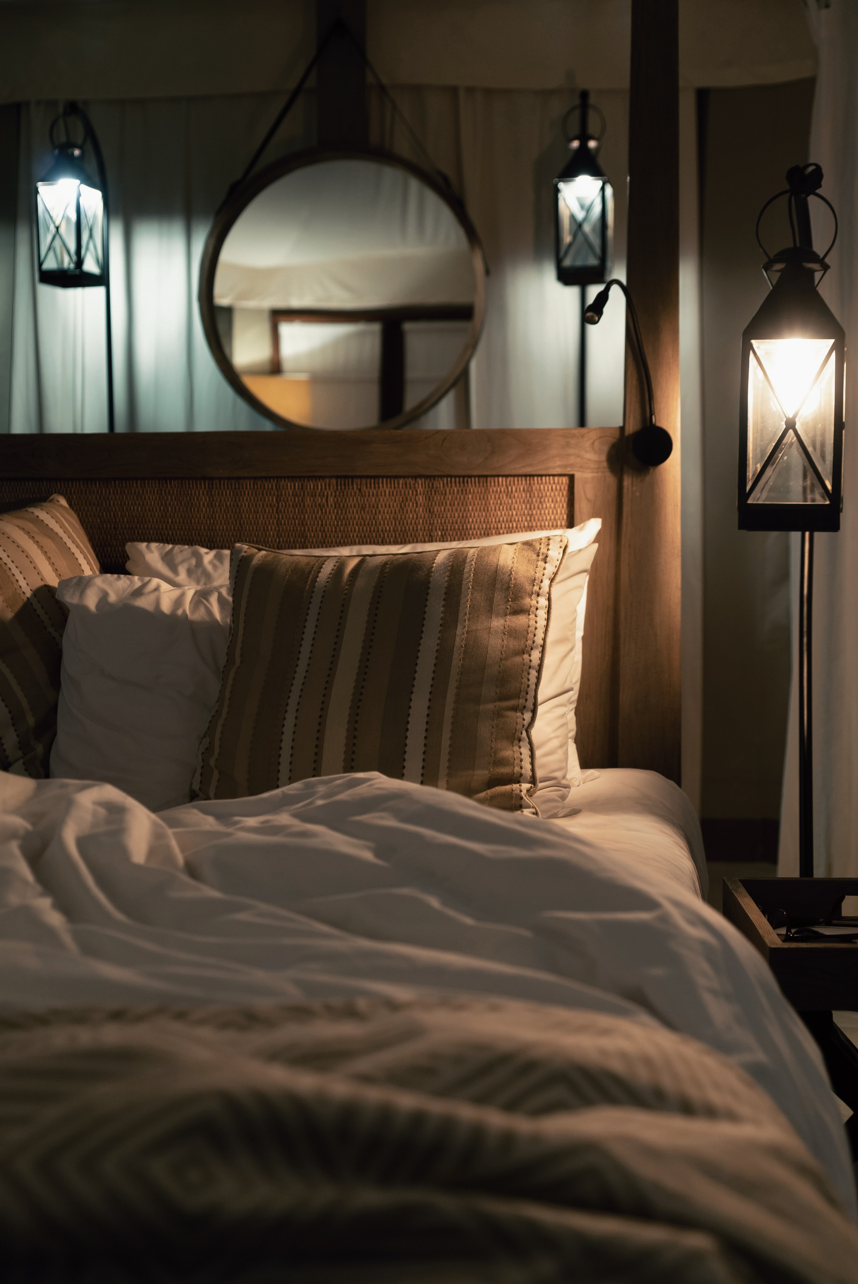 multicolored pillows on bed and lighted pendant lamp inside room