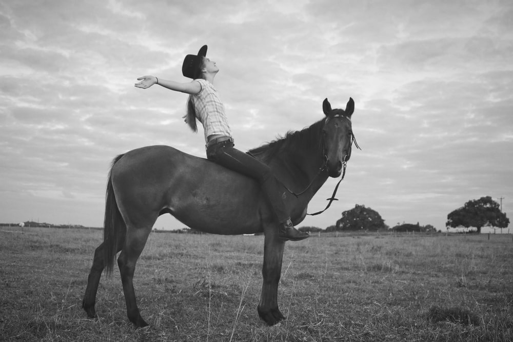 grayscale photography of woman riding horse on grass field