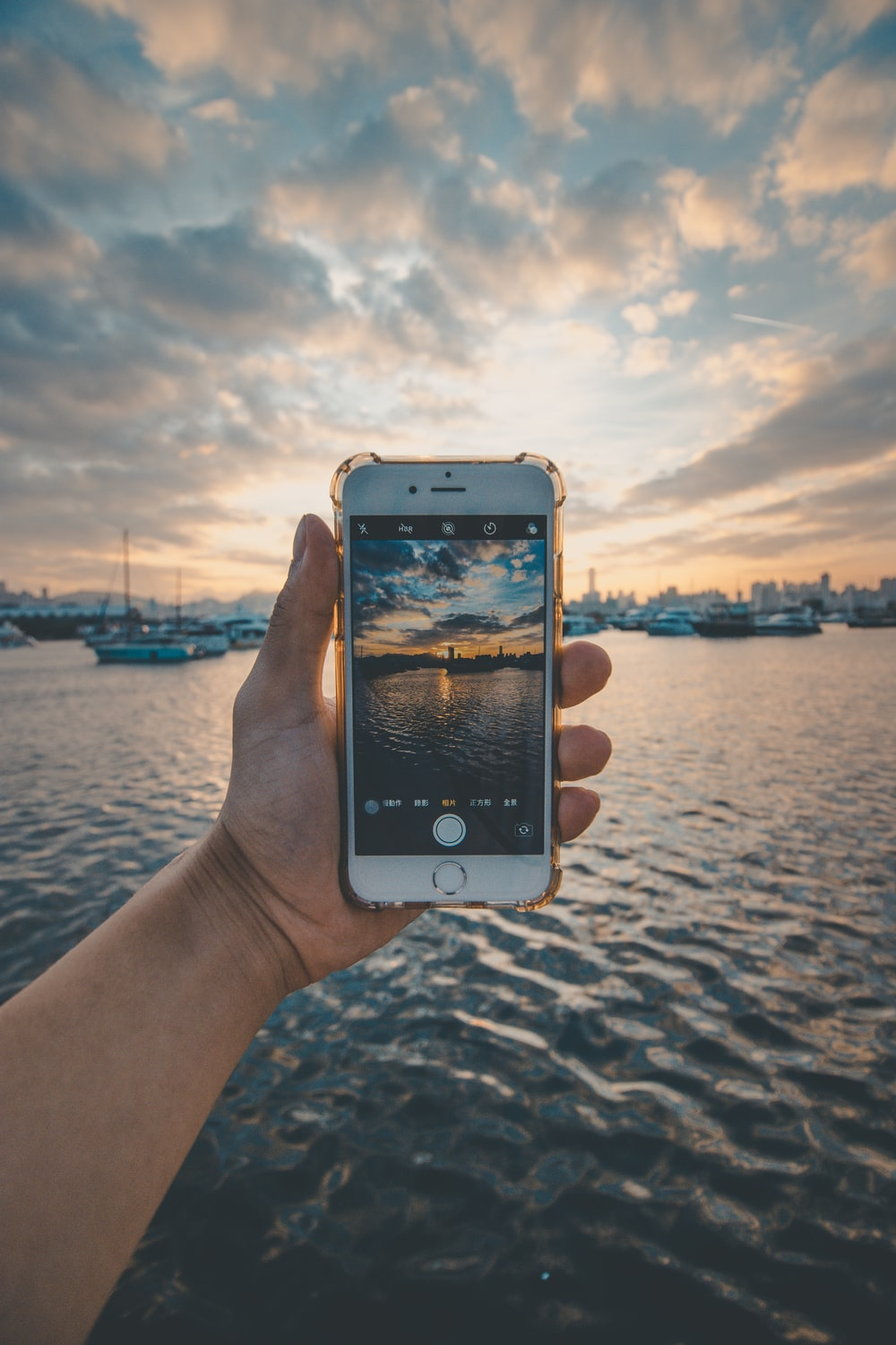 gold iPhone 6 held over the water at harbor