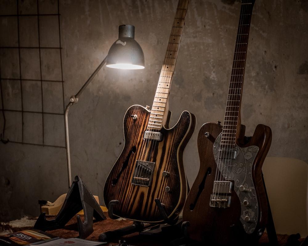 two brown guitars beside desk lamp