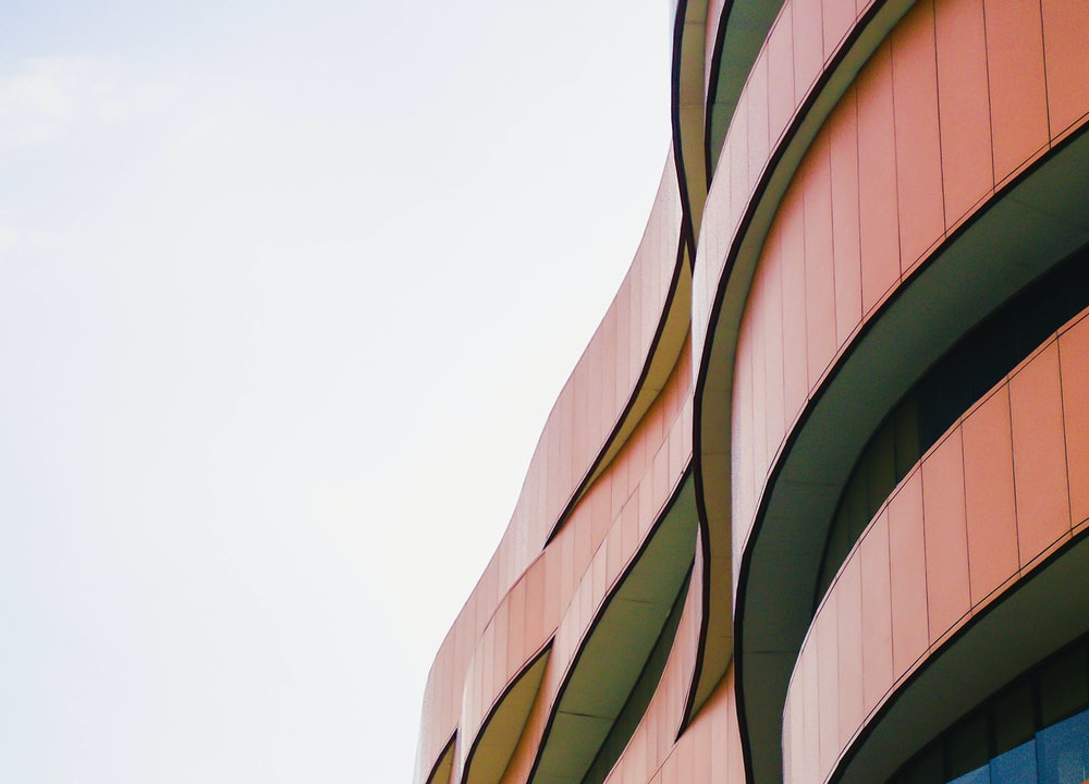 low-angle photography of red concrete multi-story building during daytime