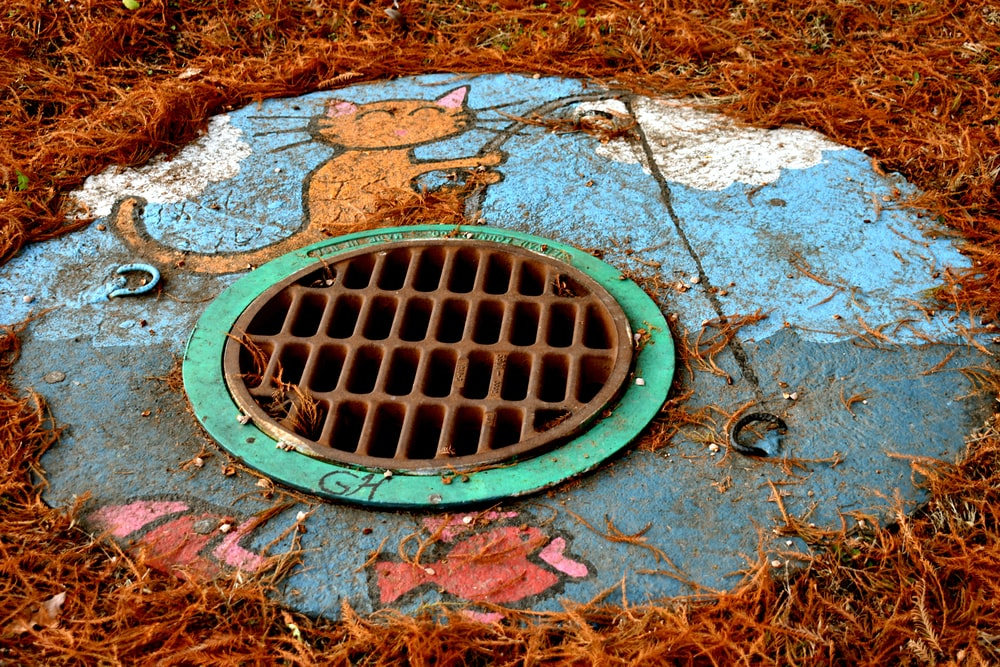 round brown and green manhole
