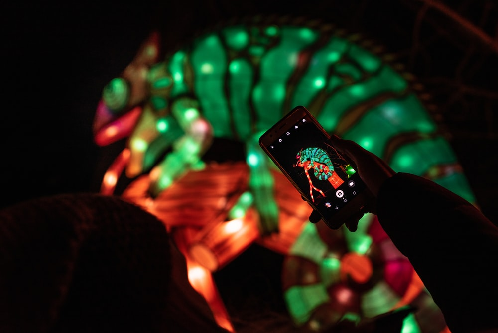 person holding turned-on smartphone at night