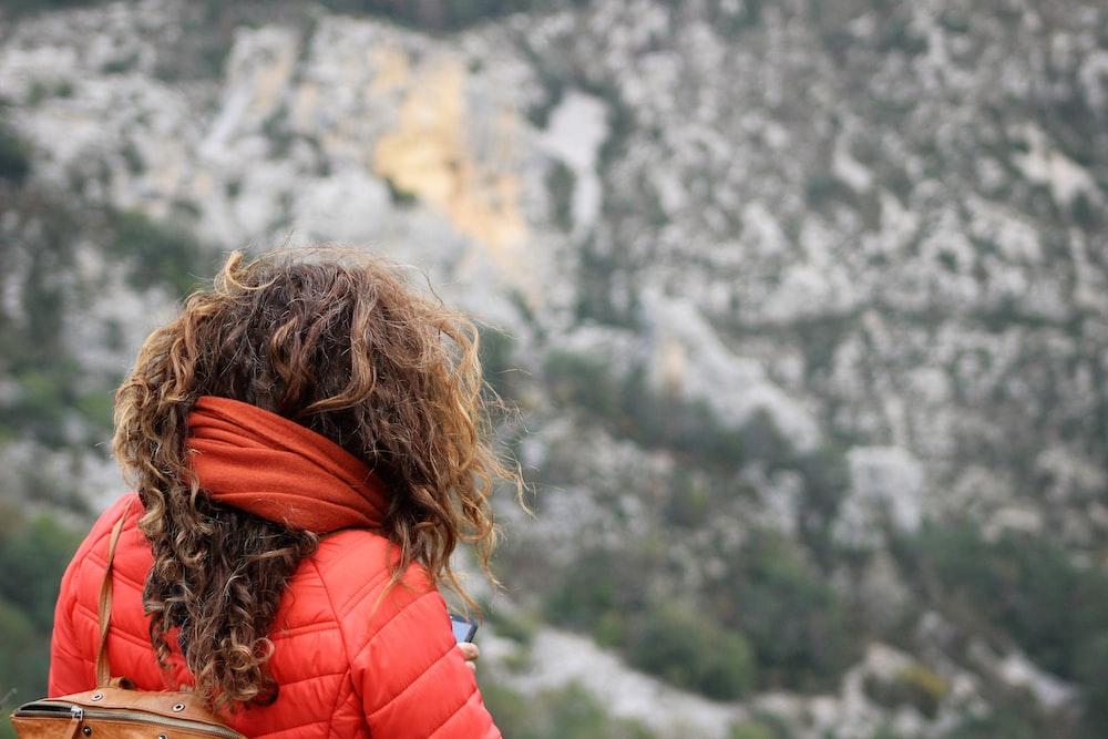 woman wearing bubble jacket near mountains