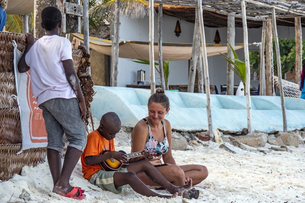 woman looking at boy playing guiatr