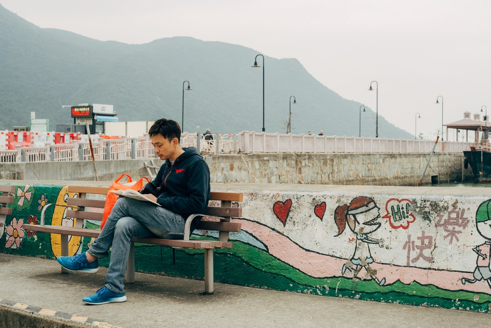 man reading book while sitting on bench beside wall with mural during day