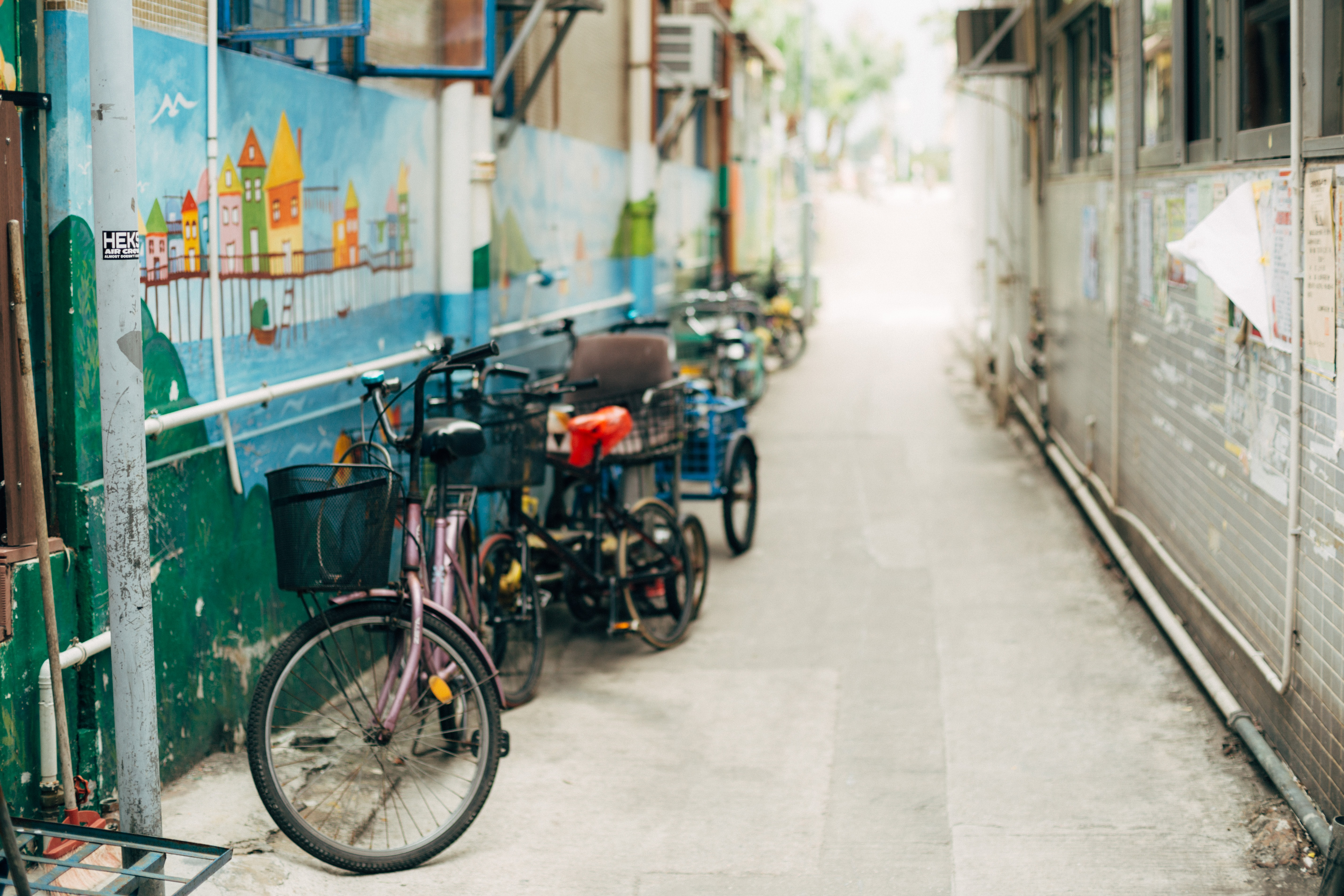 selective focus photography of bicycle parking beside wall