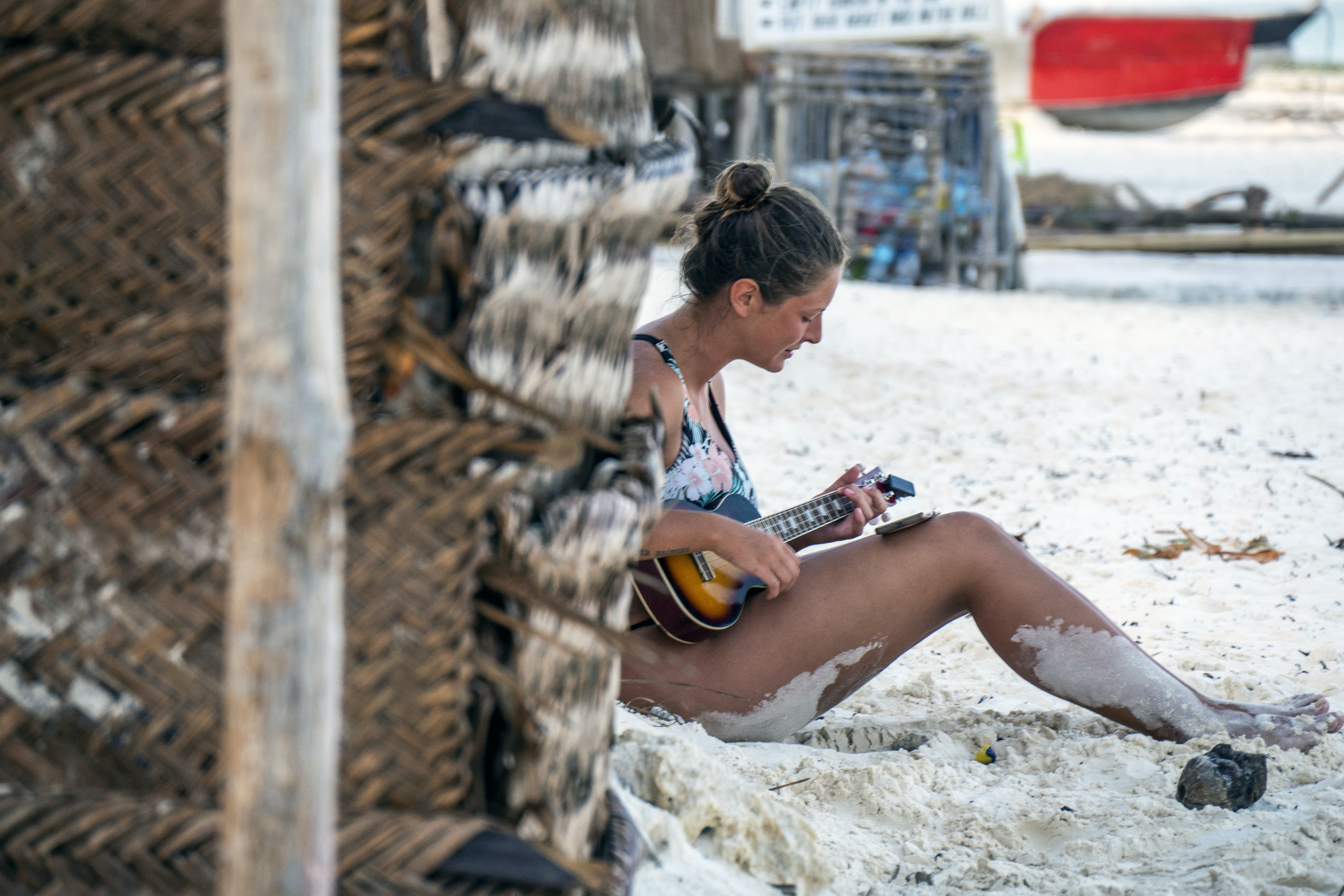woman sitting on sand while playing guitar