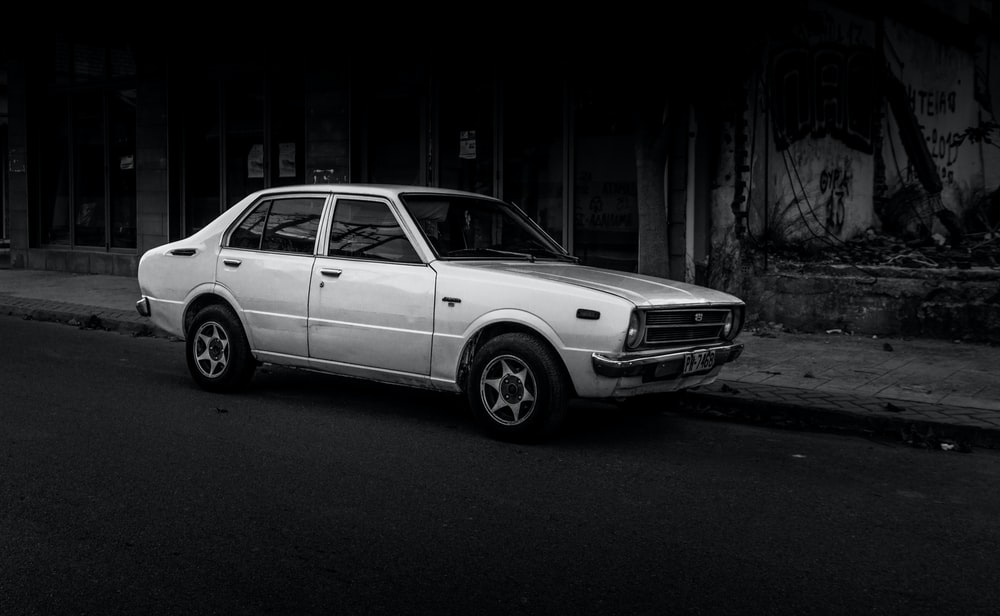 grayscale photography of sedan parking