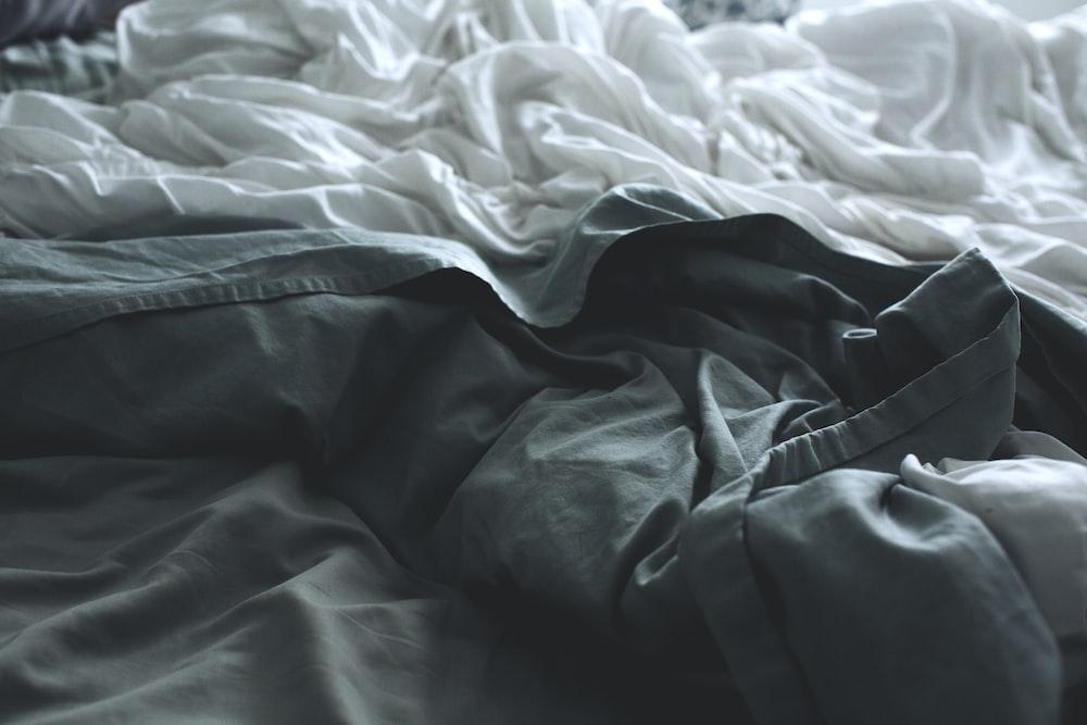 gray apparel beside white sheet