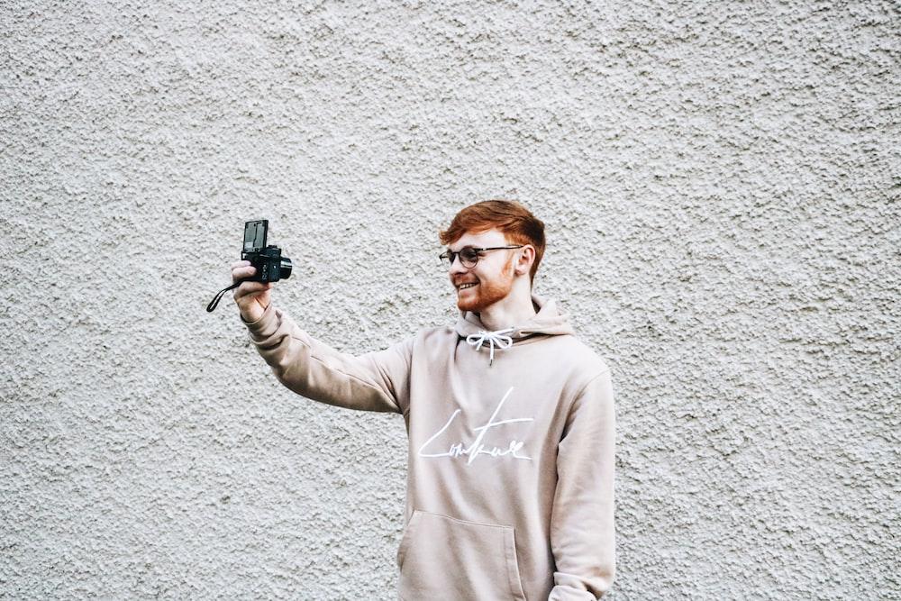man taking selfie in front of gray wall