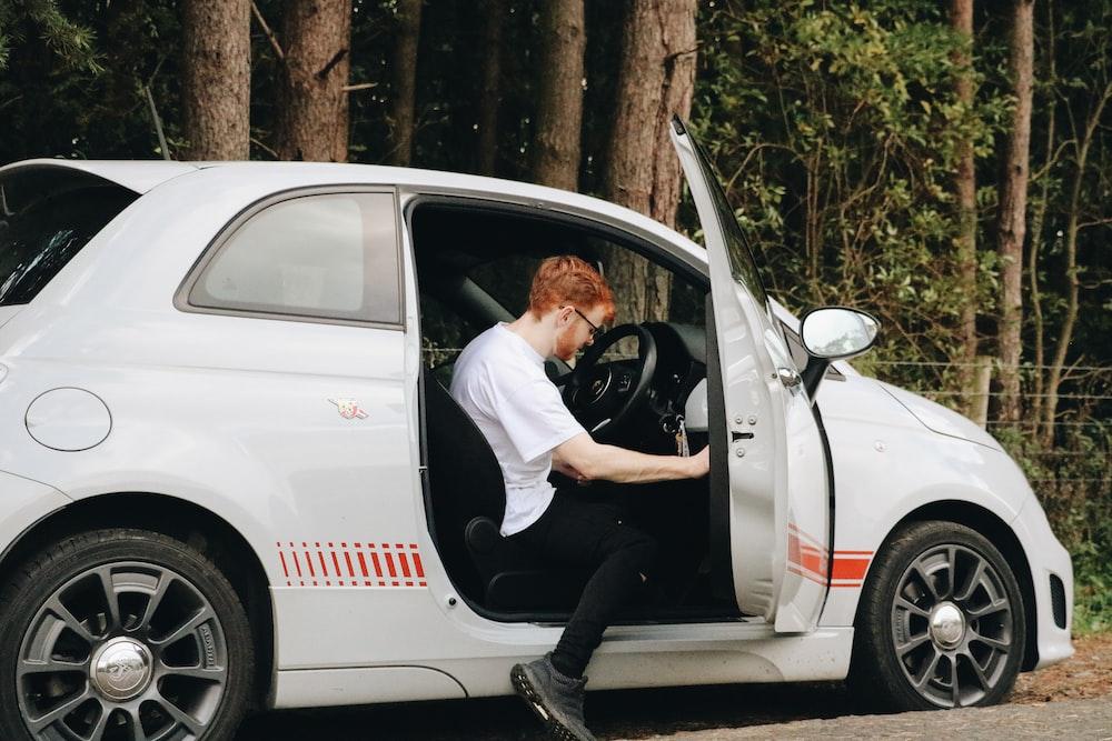 man inside white car