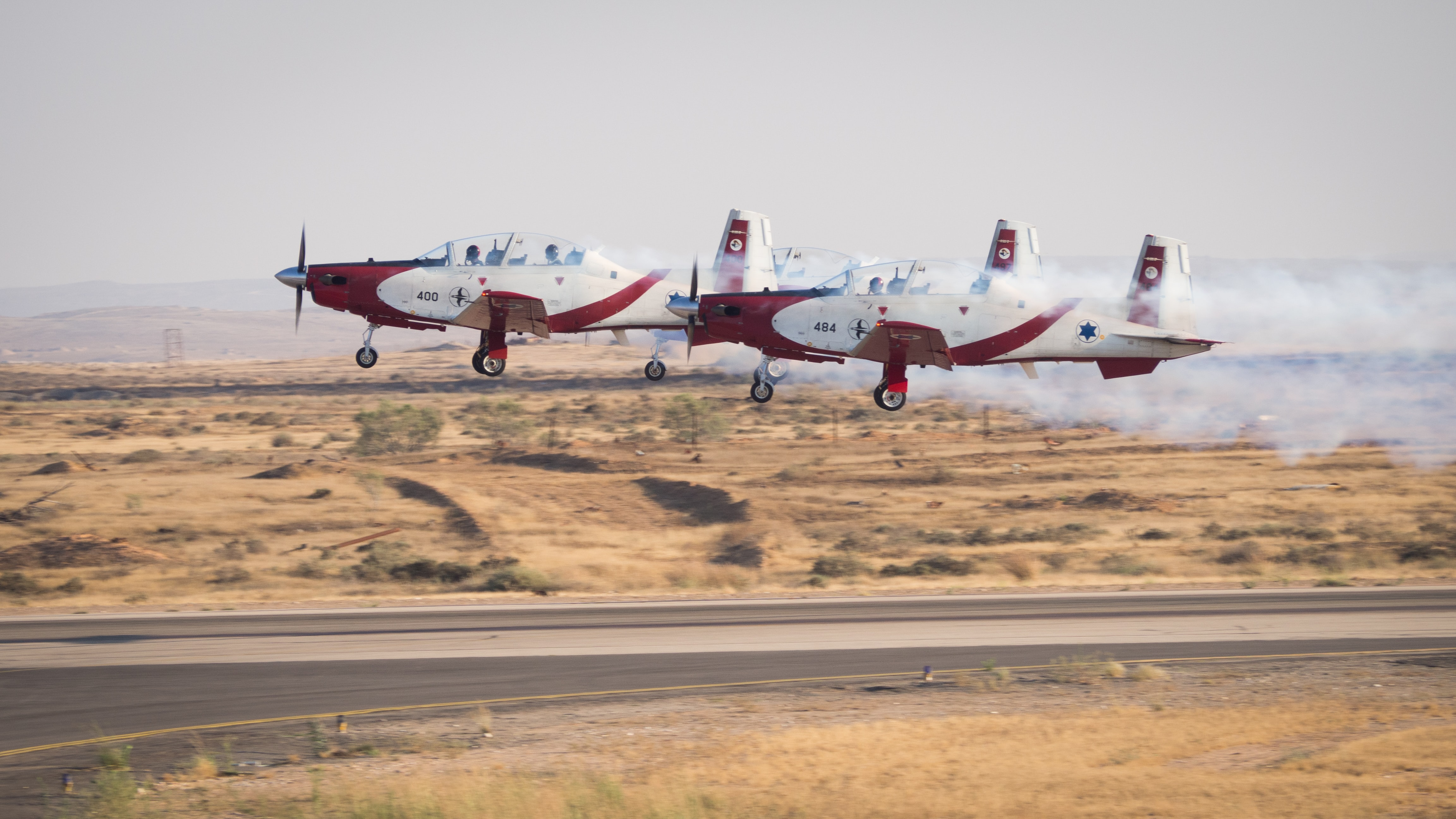 two red and white planes on dessert under white clouds