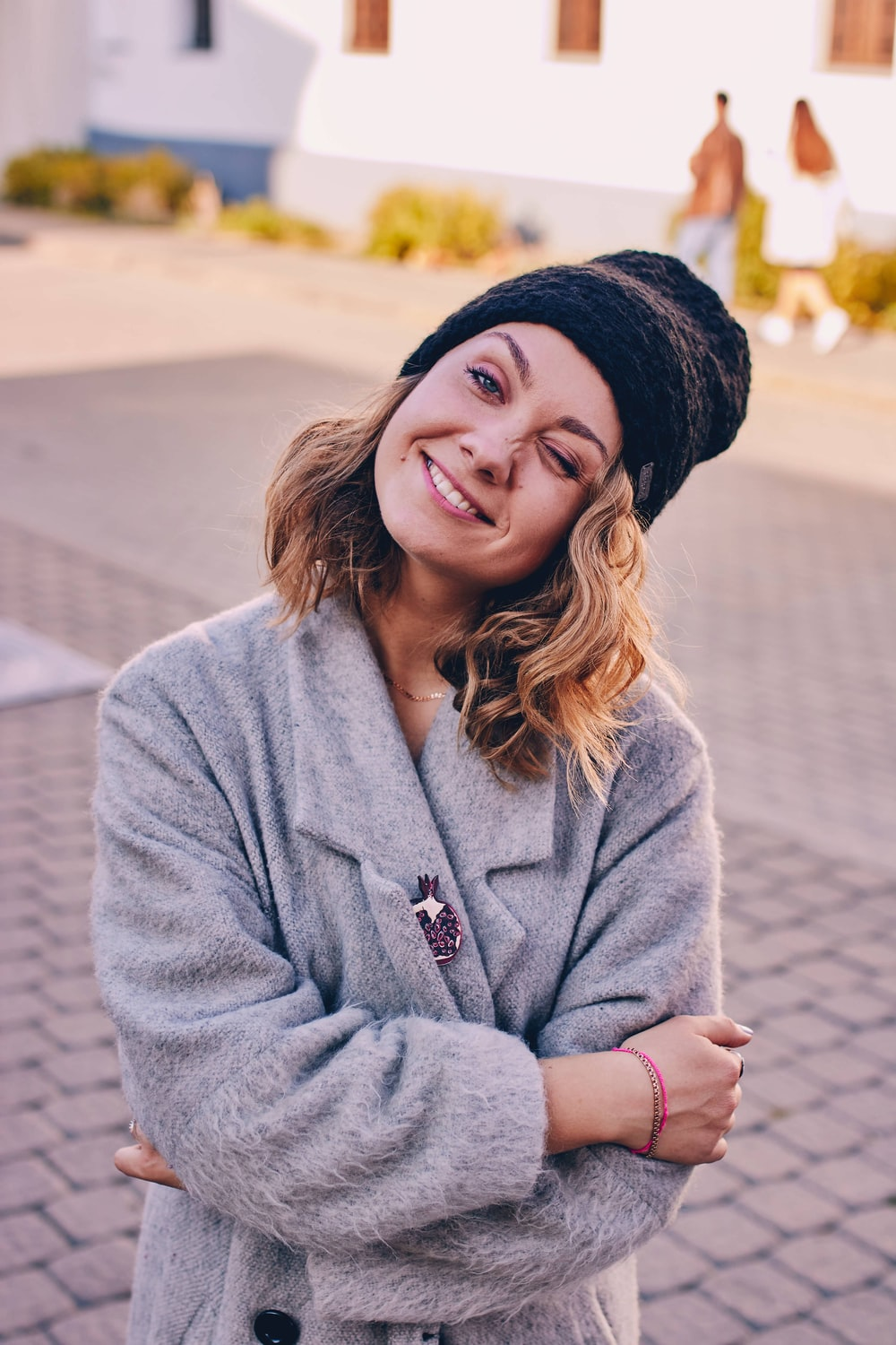 woman in gray jacket and black knit cap making face gesture