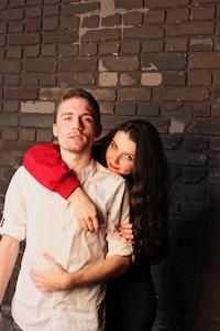 woman hugging man near brown wall
