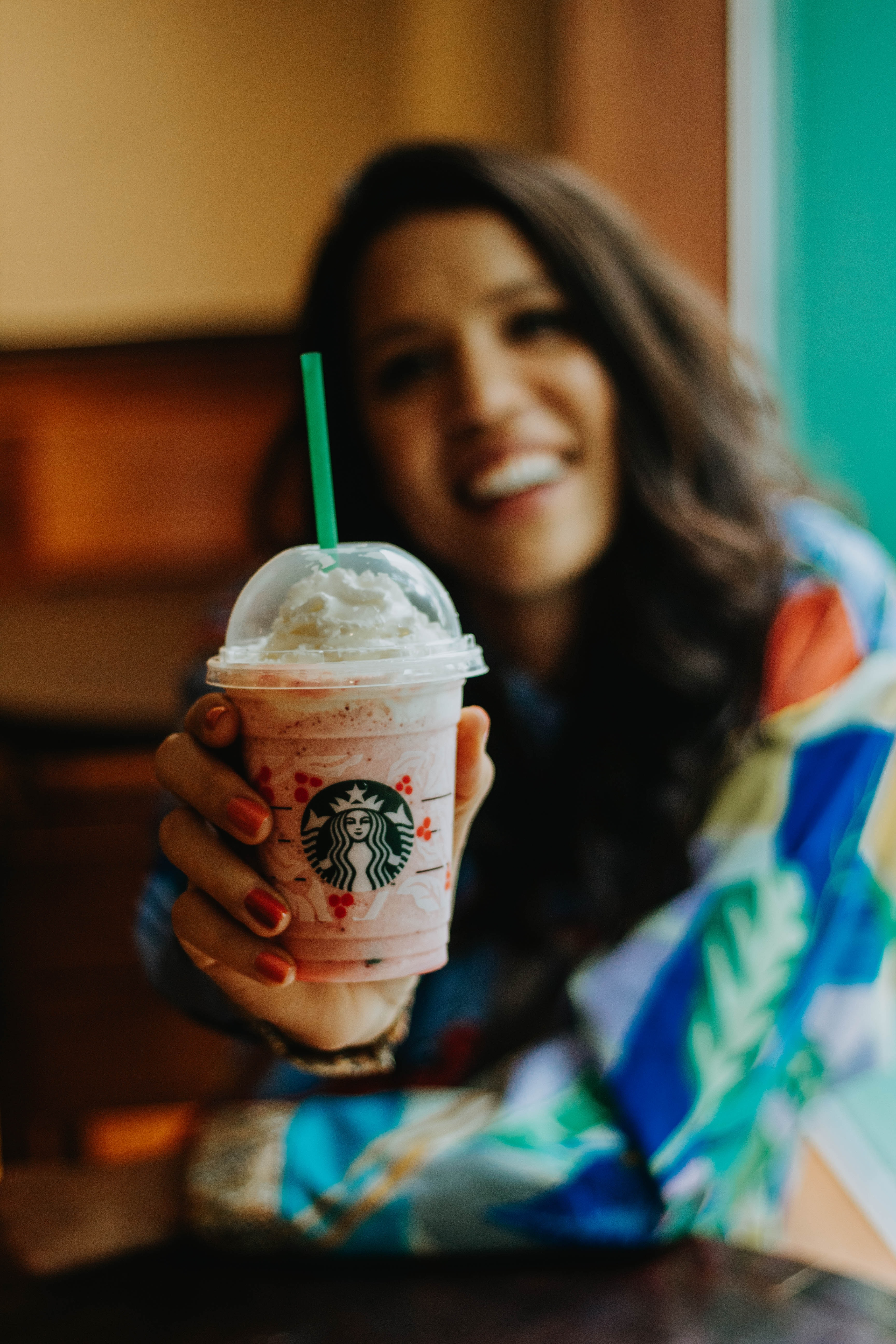 woman holding clear Starbucks disposable cup