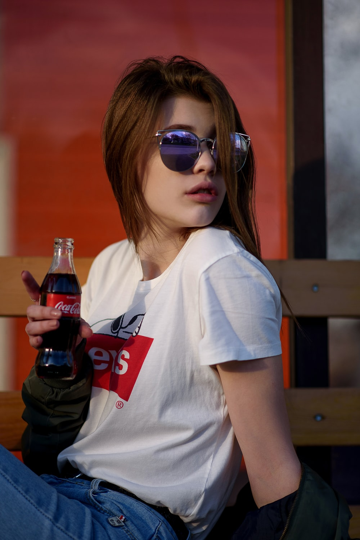 woman holding Coca-Cola bottle wearing white crew-neck Levis shirt