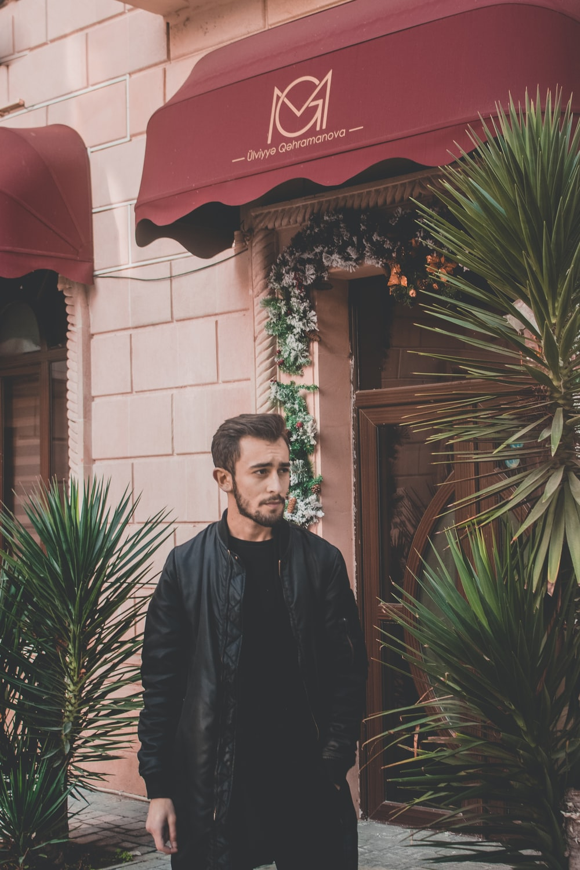 man wearing jacket standing beside plant