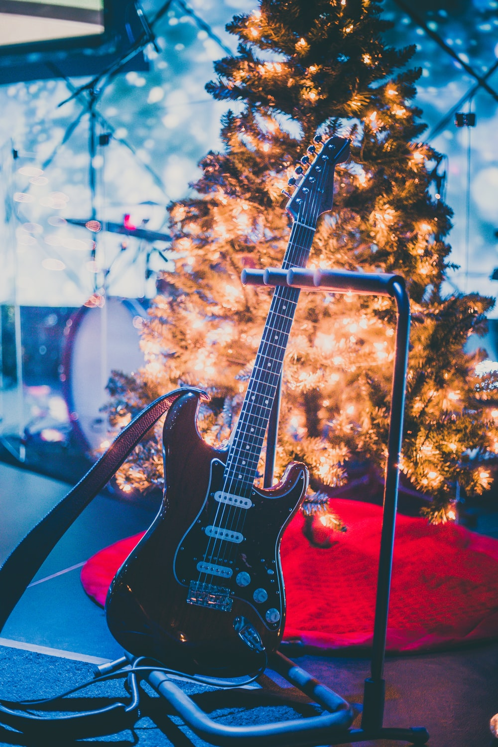 black electric guitar beside holiday tree