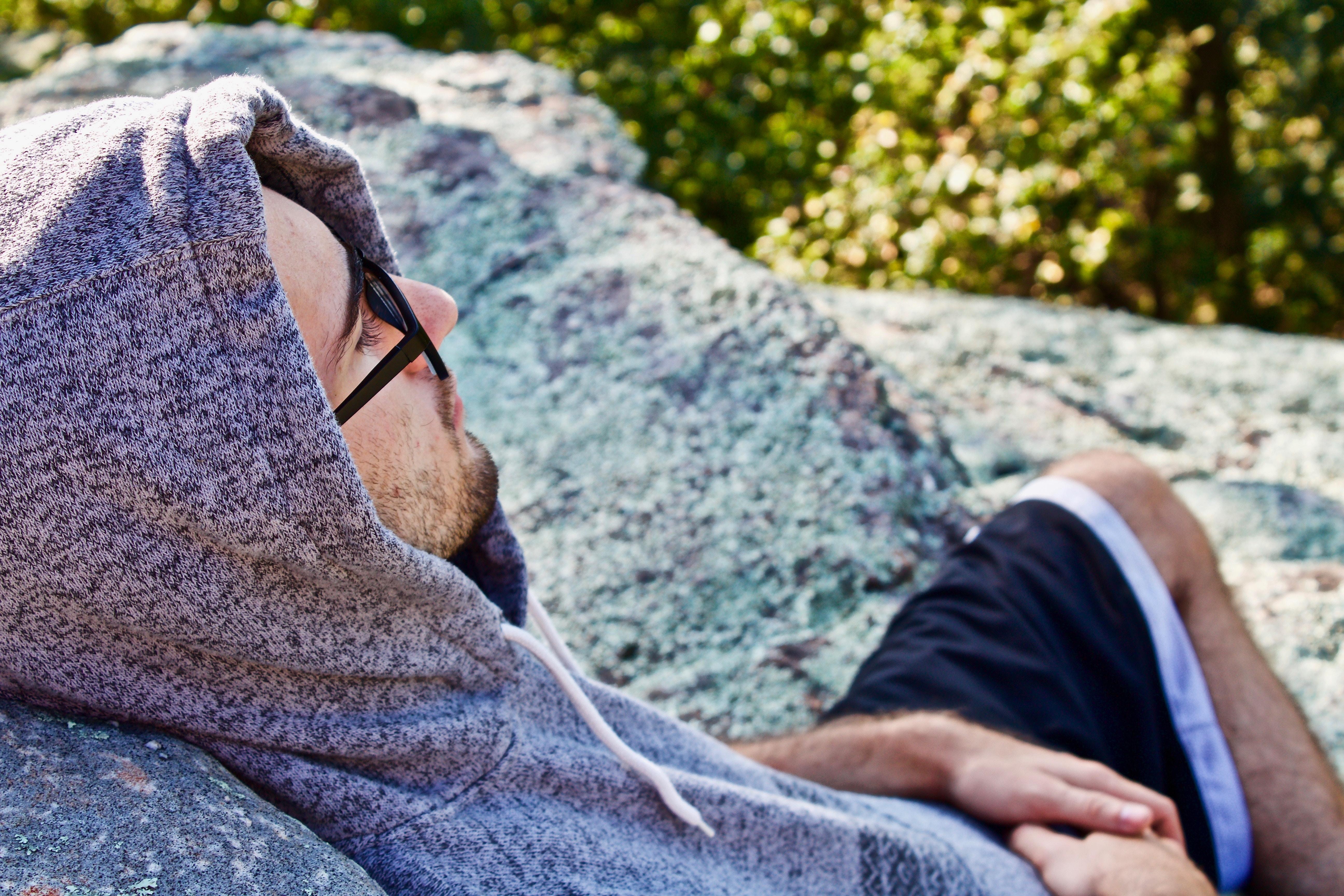 man wearing hoodie leaning on stone