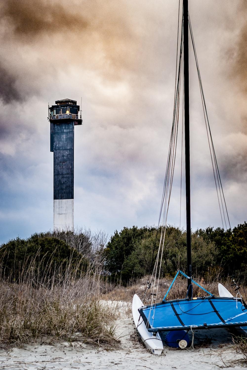 blue boat near lighthouse