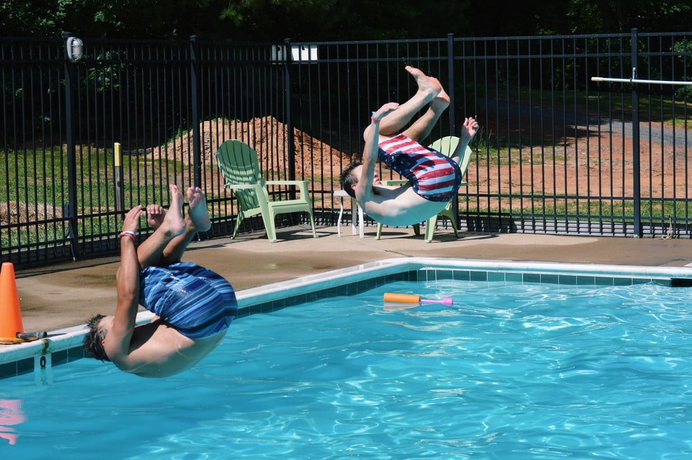 two men jumping on swimming pool