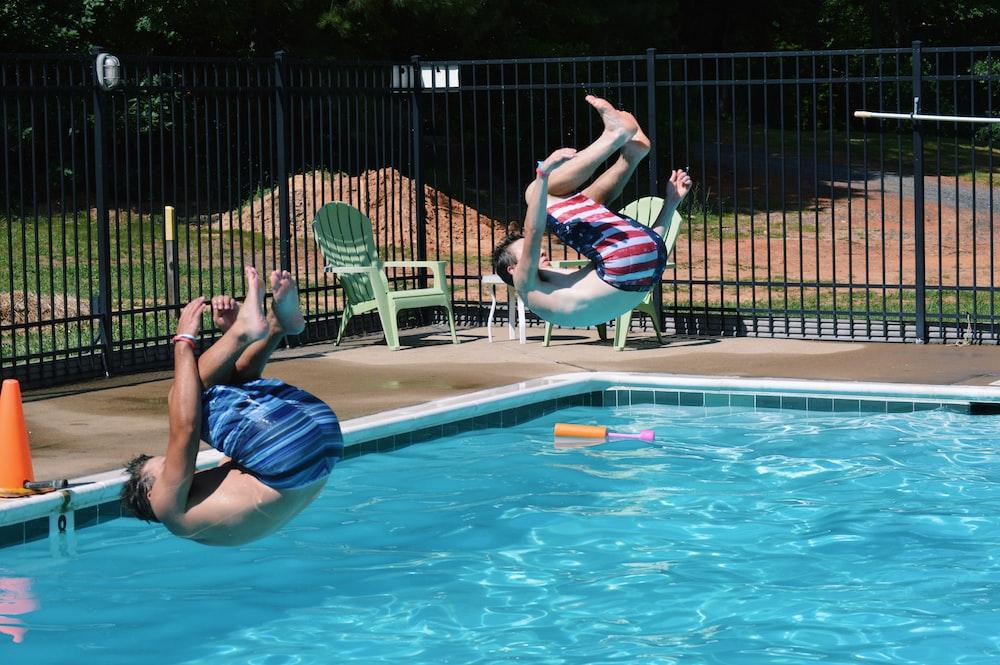 two men jumping on swimming pool
