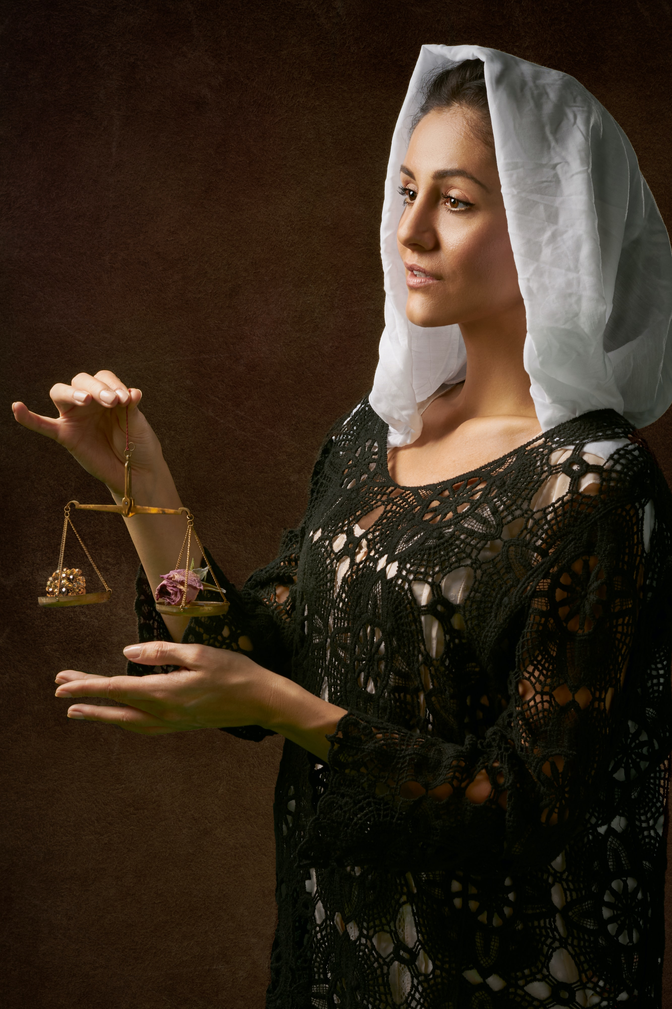 woman holding brass colored balance scale