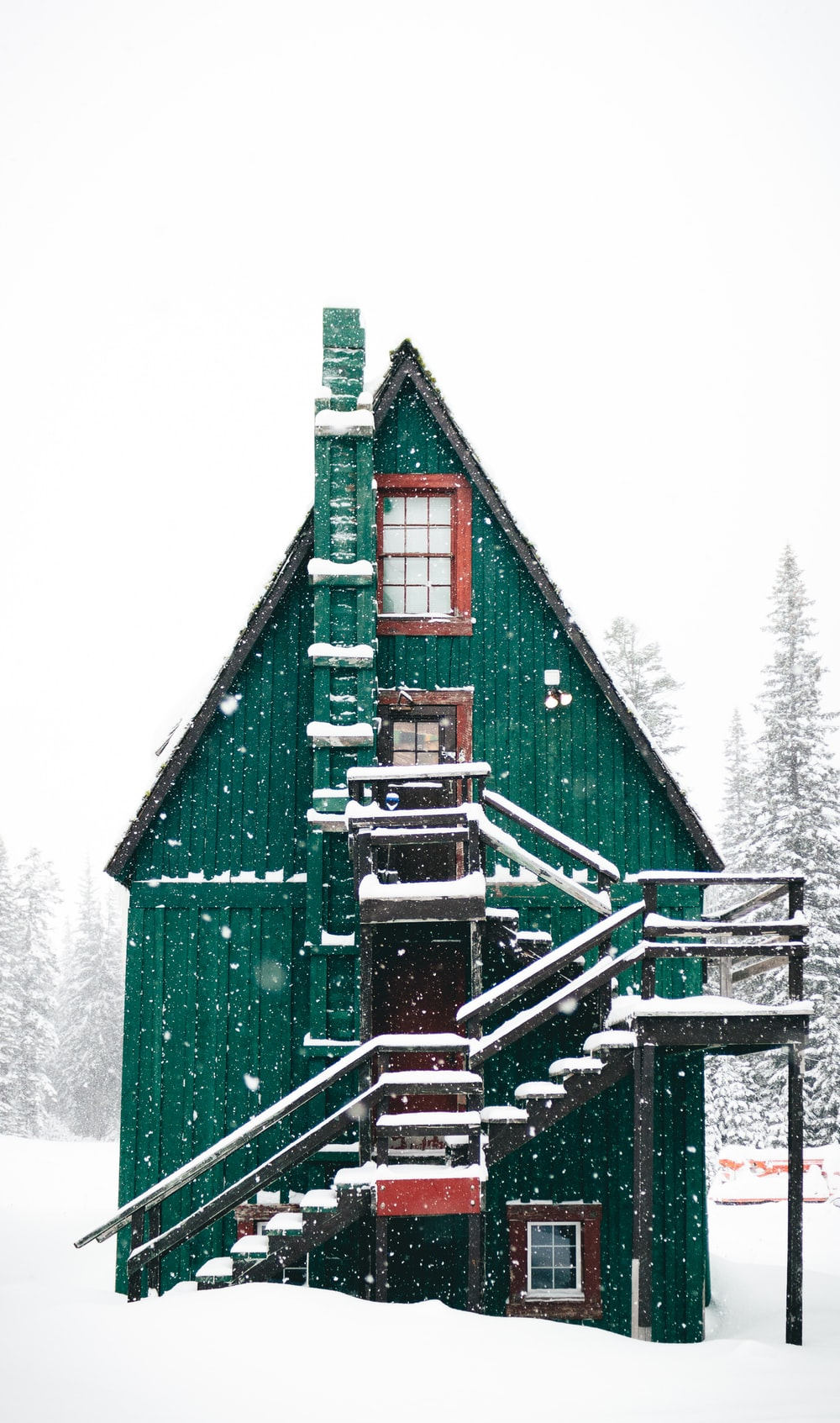 time-lapse photography of snow falling over green wooden house