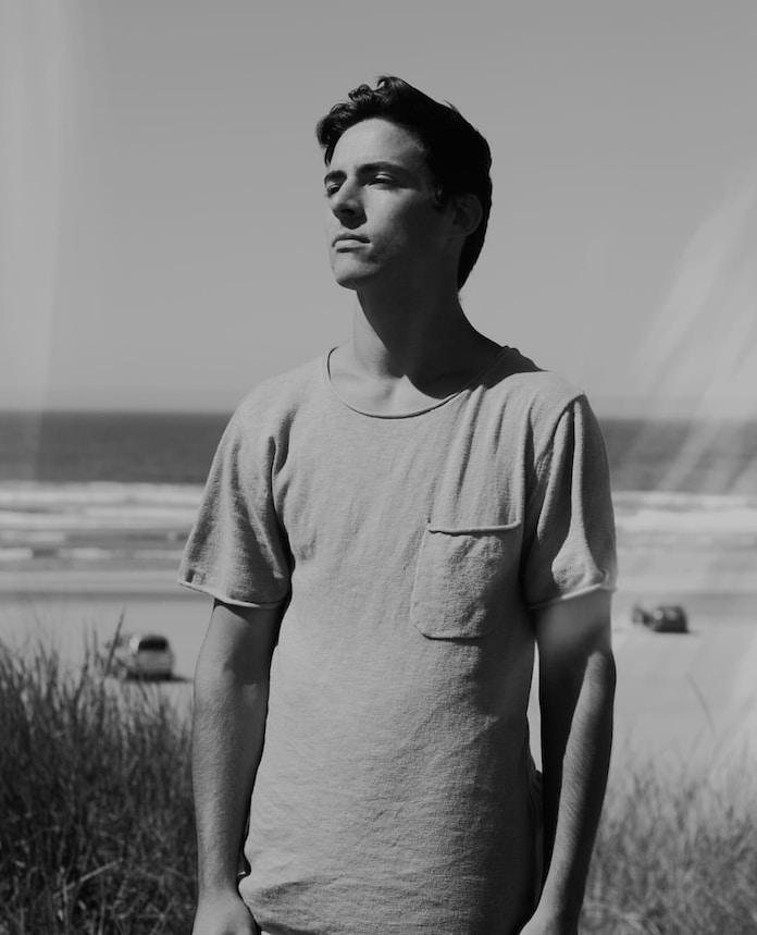 man wearing crew-neck t-shirt standing near sea