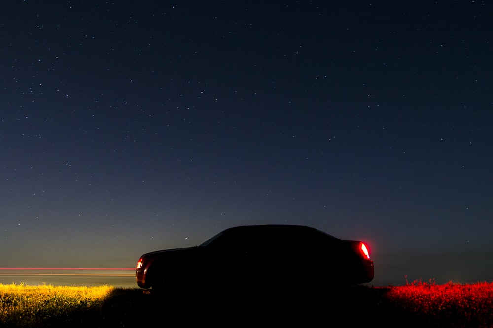 silhouette of car under starry sky during nighttime