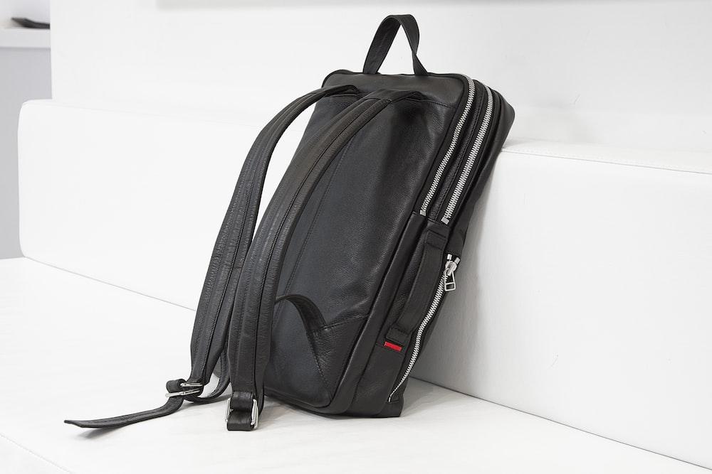 black leather backpack on white sofa