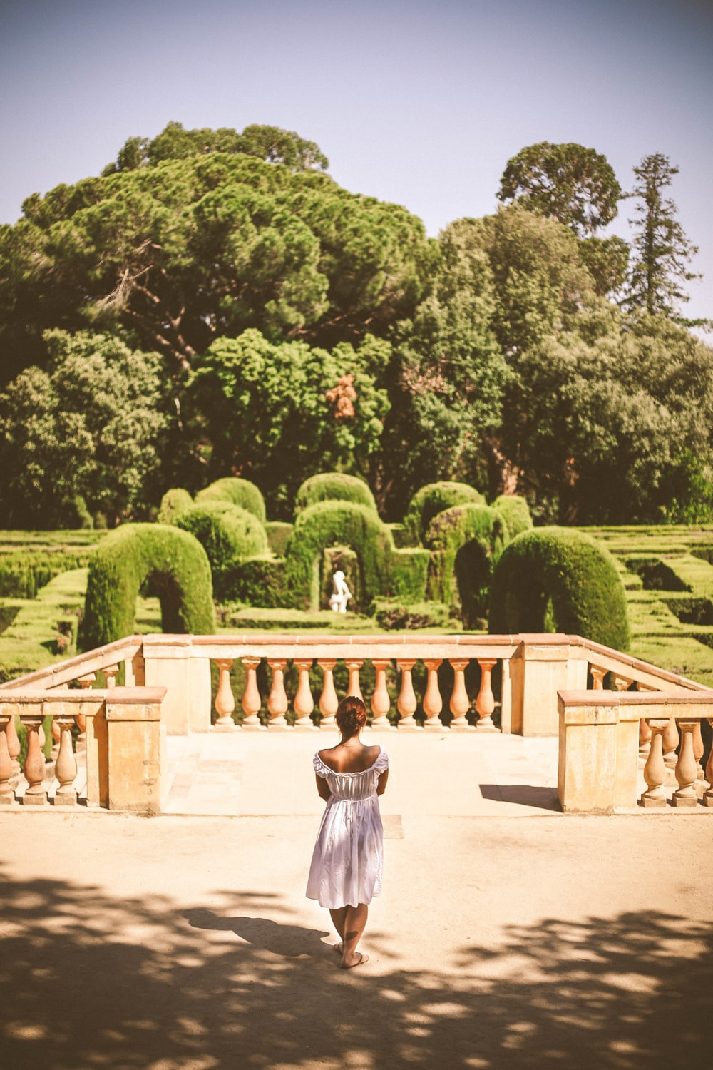 woman in white dress standing near green trees during daytime
