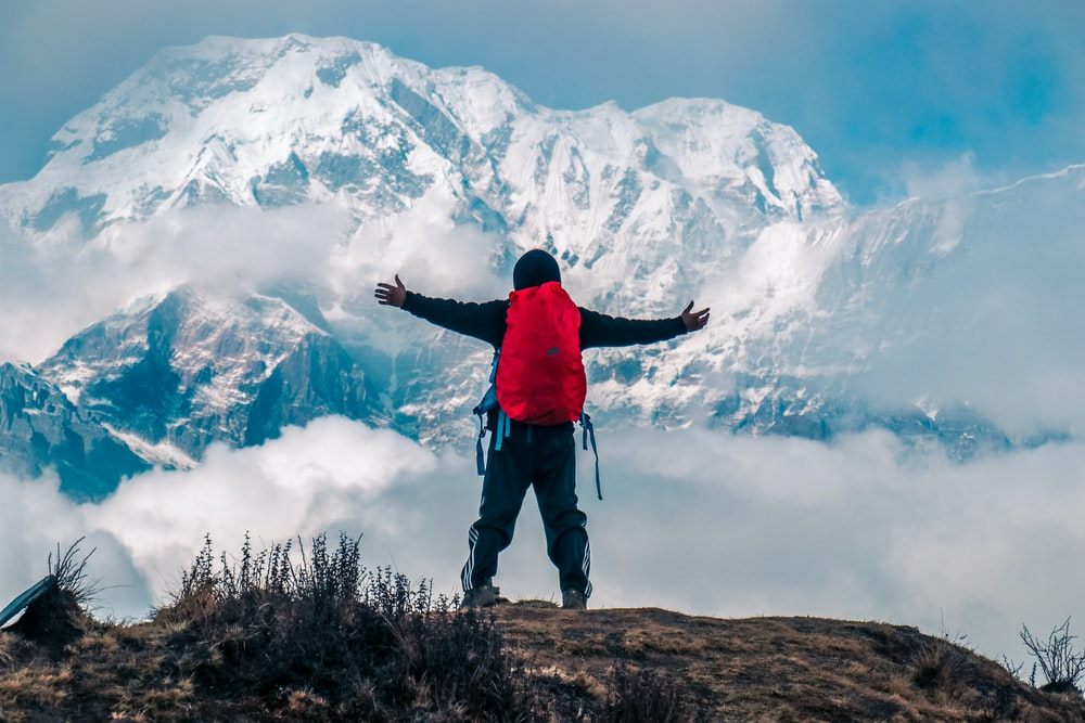 man raising both hands on mountain cliff with snow covered mountain view