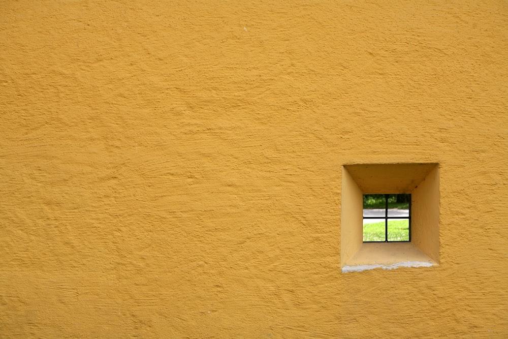 glass window pane with yellow concrete wall