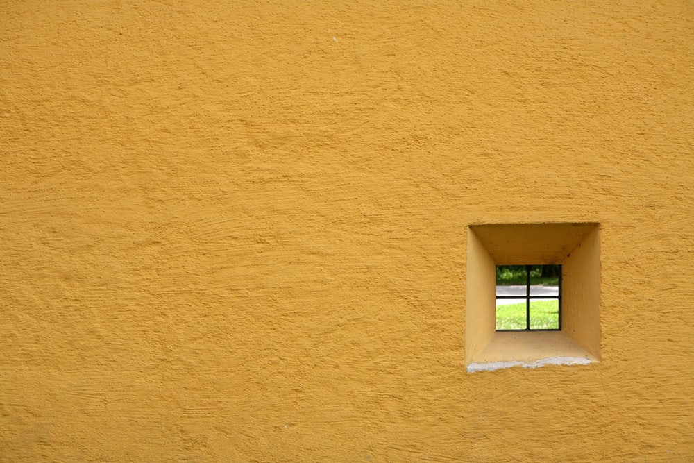 glass window pane with yellow concrete wall