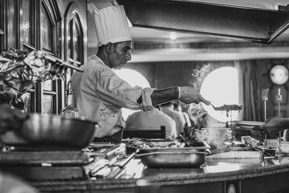 grayscale photo of man cooking
